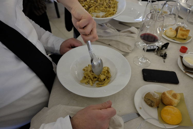 Hand Of Waiter Serving Pasta In Bowl At Restaurant