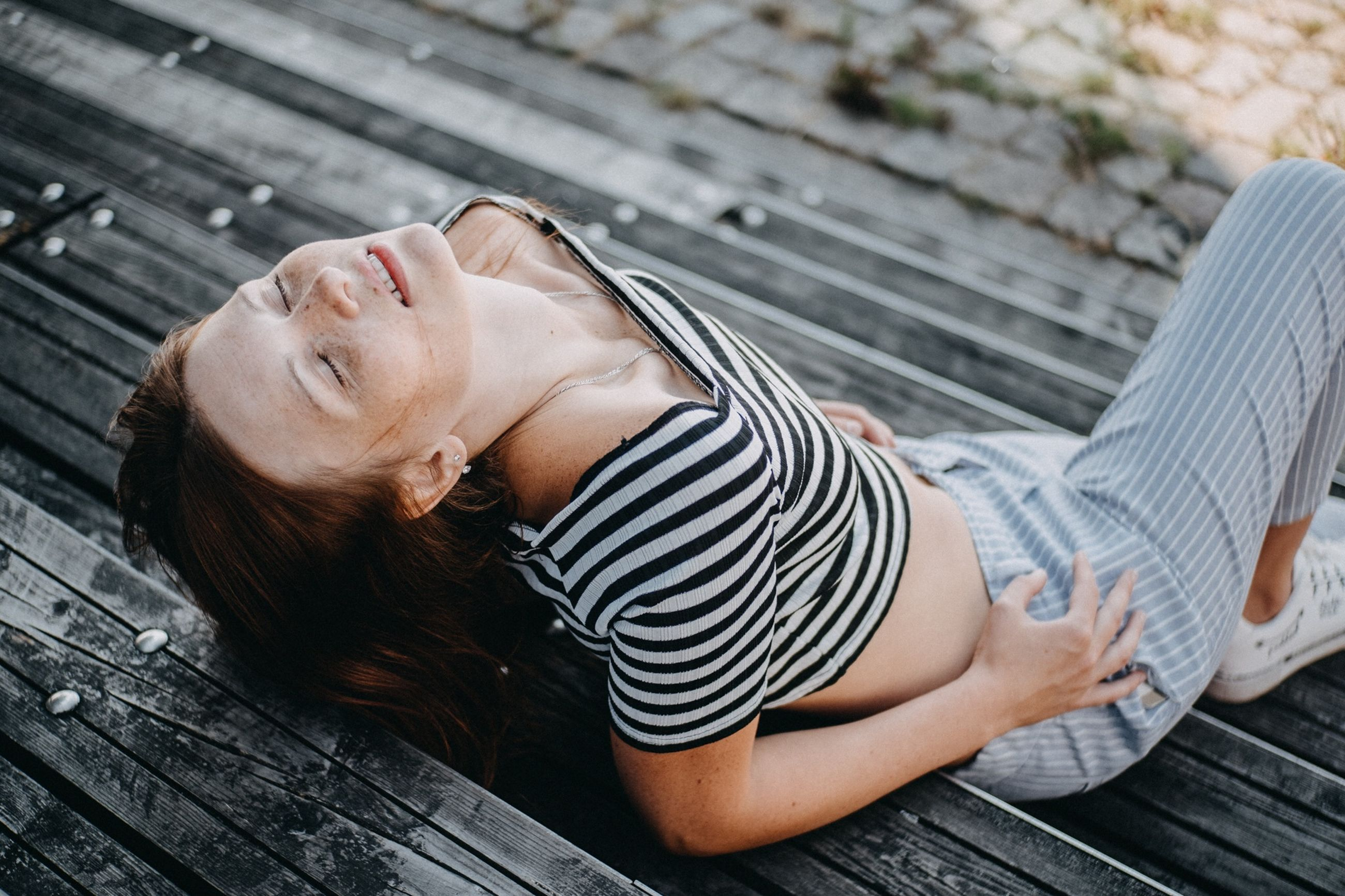 young adult, lying down, one person, relaxation, young women, real people, lifestyles, casual clothing, adult, leisure activity, three quarter length, women, day, lying on back, eyes closed, smiling, high angle view, striped, resting, outdoors, beautiful woman, hairstyle