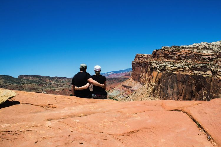sitting arm in arm in rock in Capitol Reef NP Man Capture The Moment Arm In Arm Together Togetherness Friendship Friends Love Couple Red Rocks  Mountain Pair USA Unites States Woman Watching Sand Dune Clear Sky Togetherness Sand Blue Sitting Desert Sky Namib Desert Geology Friend Arid Landscape Rock Formation Sandstone