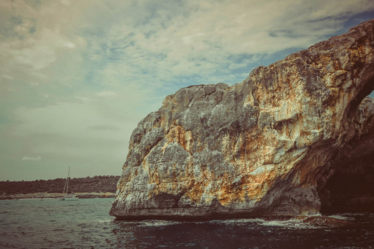 Rock Sea Water Rock - Object Rock Formation Sky Cloud - Sky Solid Tranquility Scenics - Nature Nature Tranquil Scene Beauty In Nature No People Day Land Non-urban Scene Cliff Beach Outdoors Formation Eroded Cinematic Grain Sea Caves