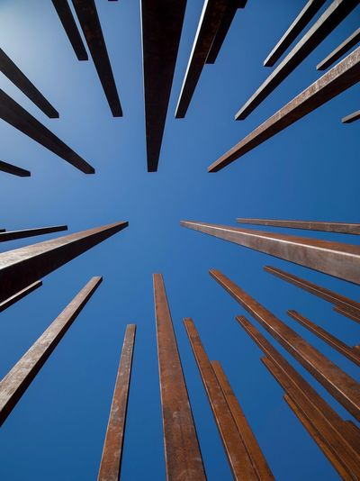 Low angle view of wooden post against clear blue sky