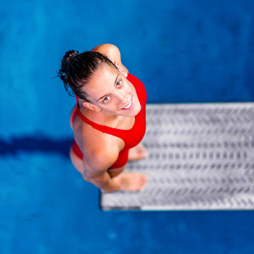 Female Diver Standing On The Jumping Board Diving Diver Swimming Pool Woman Water Sport Training Competition Young Exercising Diving Board Board Above Action Swimwear Blue Activity Muscular Build Extreme Sports Caucasian Ethnicity Athlete Square Red Smiling
