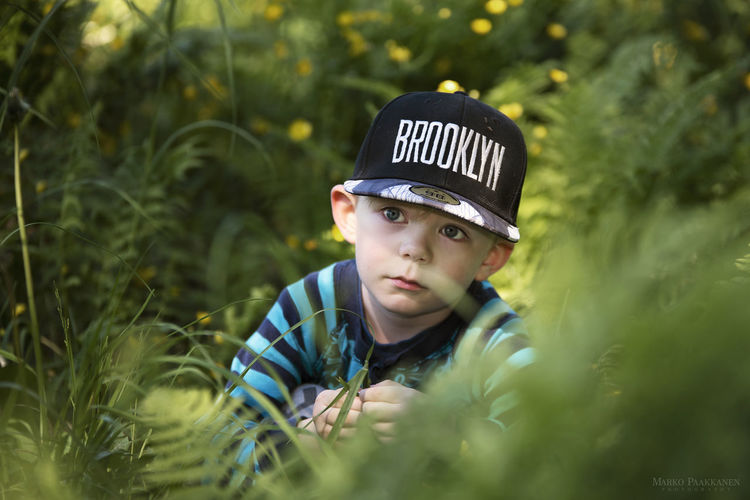 The Portraitist - 2018 EyeEm Awards Boys Cap Casual Clothing Child Childhood Clothing Contemplation Day Front View Green Color Hat Headshot Innocence Looking Males  Men One Person Outdoors Plant Portrait Real People Selective Focus