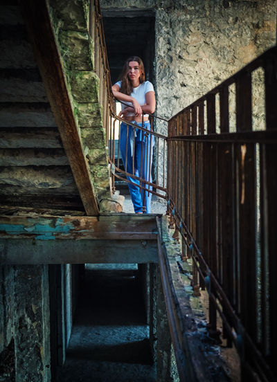 Portrait of woman standing on staircase of building