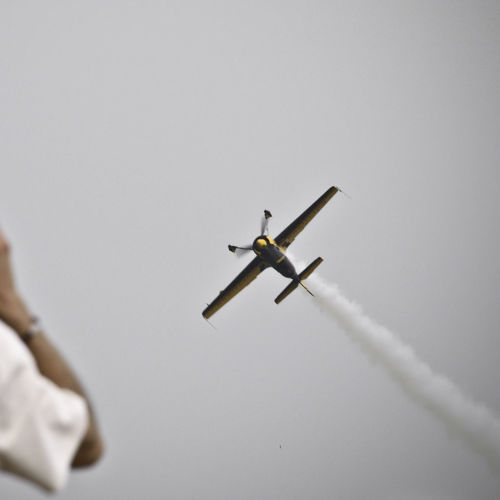 Low angle view of propeller airplane with vapor trail during airshow