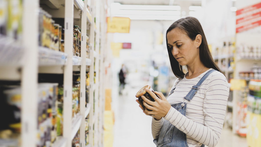 Side view of woman looking at bottle in supermarket