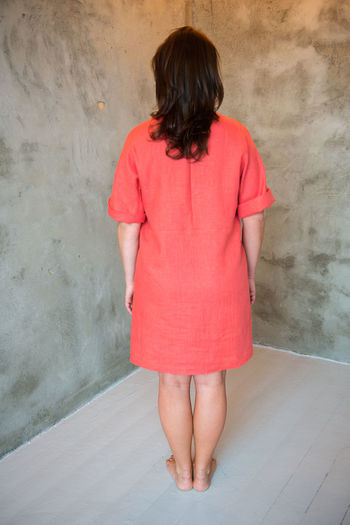 Woman In Red Dress Standing Against Wall