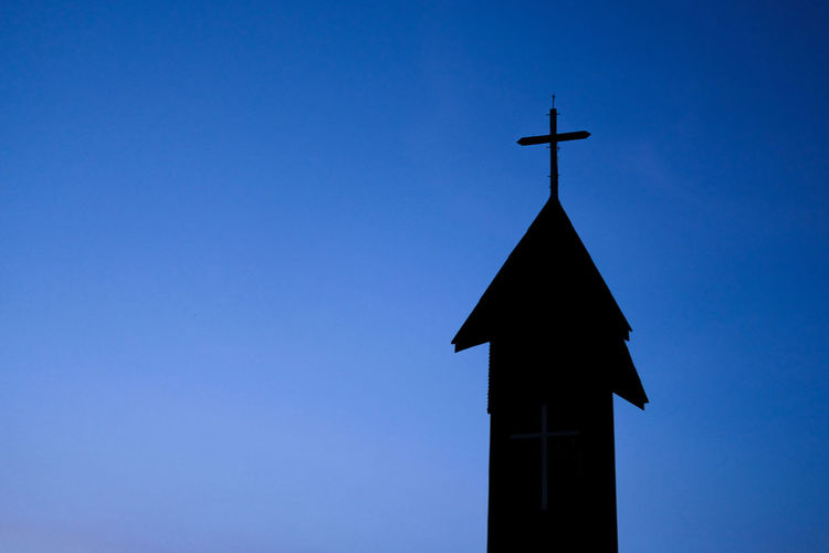 Low angle view of cross on building against blue sky