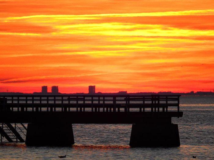 Silhouette pier over sea against orange sky