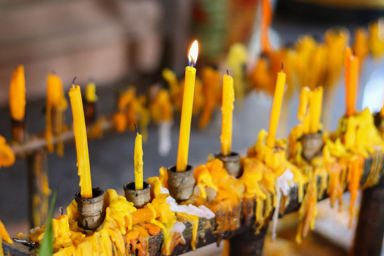 Close-Up Of Yellow Candles In Temple