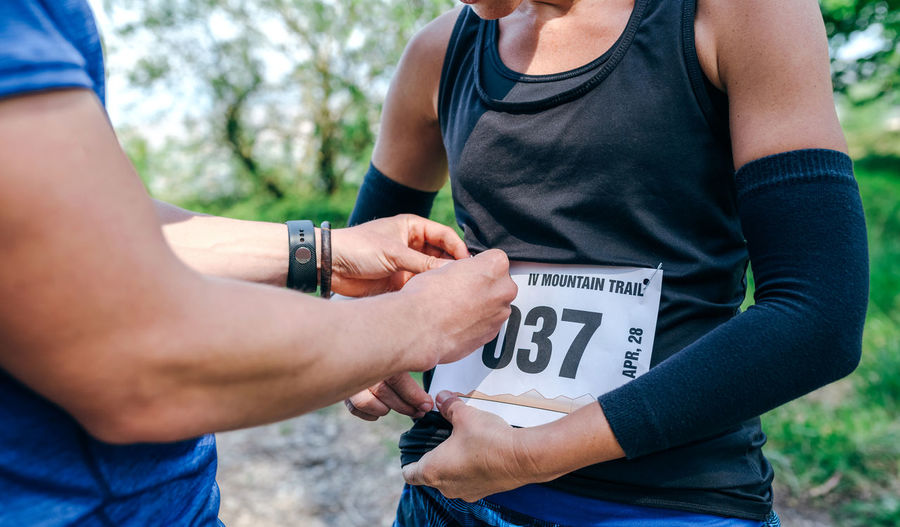 Midsection of woman attaching marathon bib while standing in forest