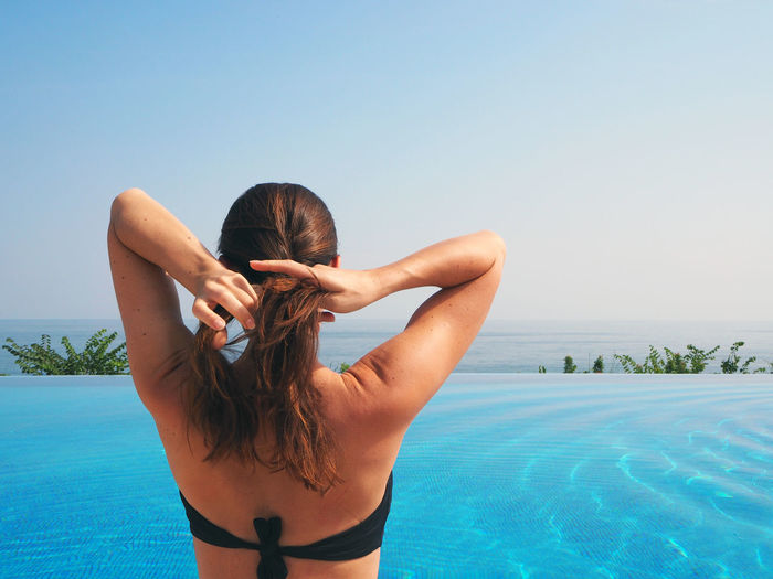 Rear view of woman adjusting hair by infinity pool against clear sky