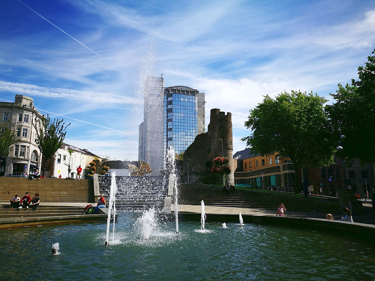 architecture, built structure, fountain, water, building exterior, splashing, sky, large group of people, waterfront, city, motion, spraying, real people, travel destinations, day, vacations, cloud - sky, outdoors, skyscraper, lifestyles, modern, nature, tree, people