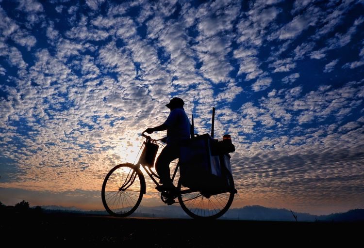 Man riding bicycle with sky morning on background