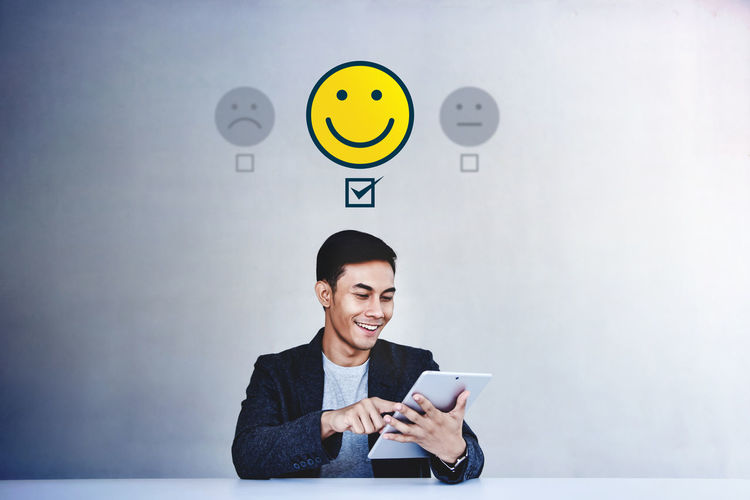 Customer Experience Concept. Young Businessman Giving his Positive Review in Satisfaction Online Survey. Happy Client Submit a Smiling Face for Excellent Services via Tablet Smiling Communication Happiness One Person Wireless Technology Emotion Holding Technology Young Adult Indoors  Front View Adult Portrait Connection Wall - Building Feature Young Men Cheerful Clock Happy Happiness Choose Review Feedback Online Survey Customer Experiences Client Happy Customer Positive