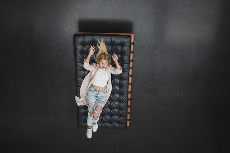 High angle view of woman lying on mattress