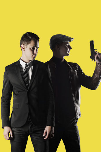 Businessman and gangster looking away while standing against yellow background
