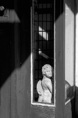 An angry looking cupid statue is peeking out of a window. Angry Art And Craft Blackandwhite Cupid Day Human Representation Mad No People Peekaboo Statue Weathered Window