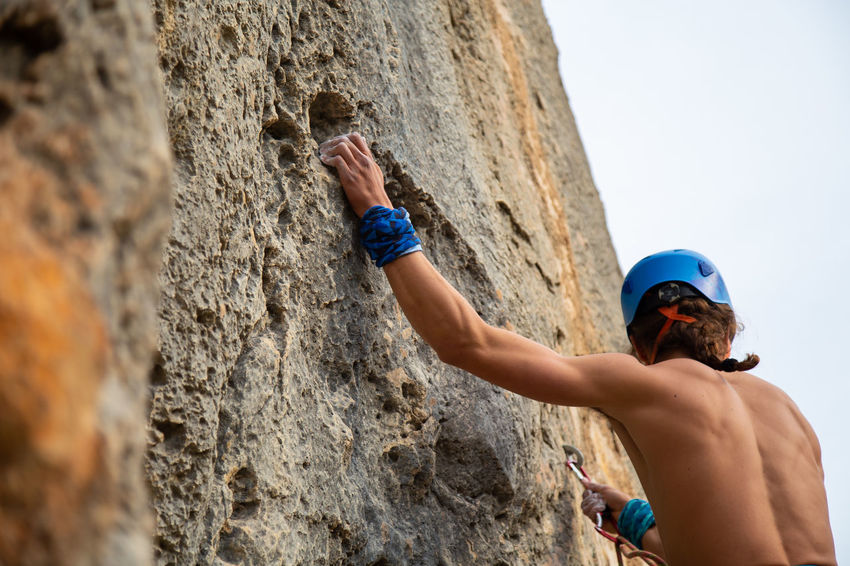 Close up hand of young man climber in a crack while climbing a wall on a sunny day. Close-up Hand Climbing Holding Powder Handhold Rock Climber Young Adult Mountain Hanging Cliff Strong Man Fingers Outdoors Extreme Sports Sport Grip Magnesium Athlete RISK Challenge Rope Caucasian