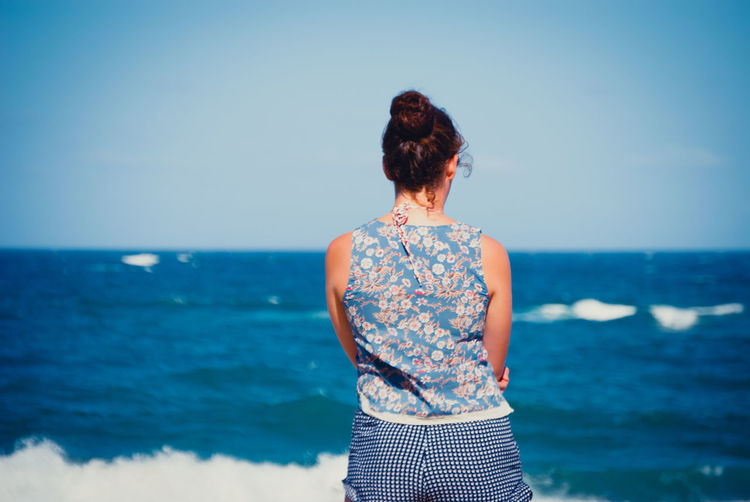 Rear View Of Woman Standing At Beach Against Clear Blue Sky
