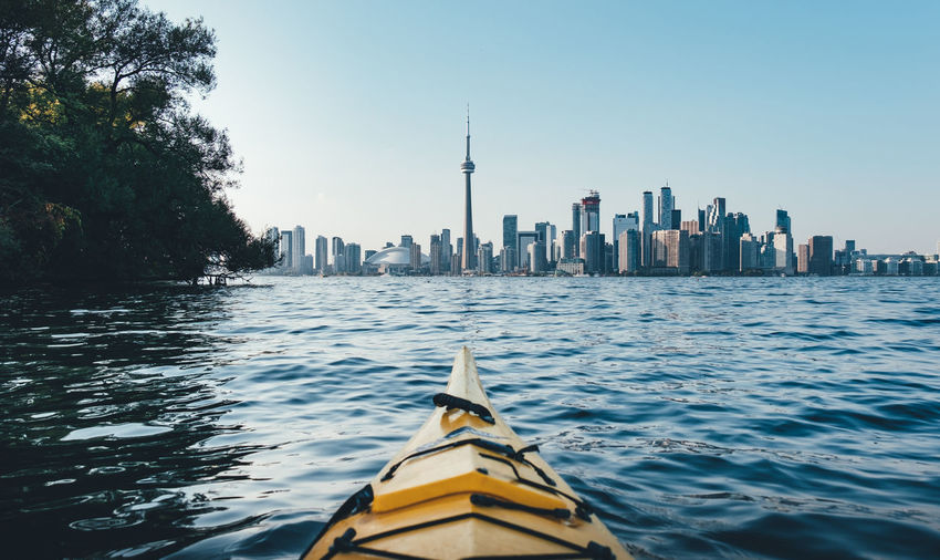 Kayak on lake by city against sky