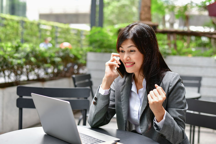 Adult Business Person Communication Computer Connection Focus On Foreground Laptop Mobile Phone One Person Portable Information Device Real People Sitting Table Technology Telephone Using Laptop Using Phone Wireless Technology Women Young Adult