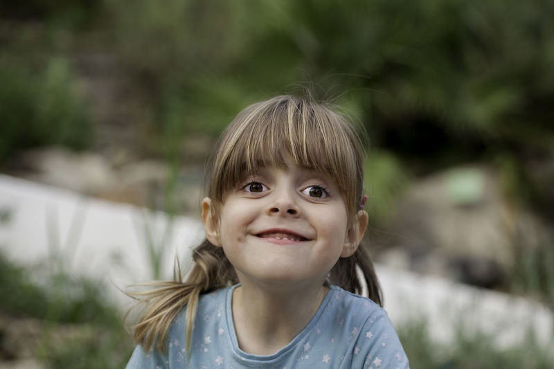 Cute little girl pulling a funny face. Blond hair female child with cheeky grin and brown eyes wearing a green top with humorous expression on a sunny day. Blond Hair Carefree Cheerful Child Childhood Children Only Close-up Cute Day Enjoyment Female Front View Funny Faces Girl Happiness Headshot Humor Kid Looking At Camera One Girl Only One Person Outdoors People Portrait Smiling