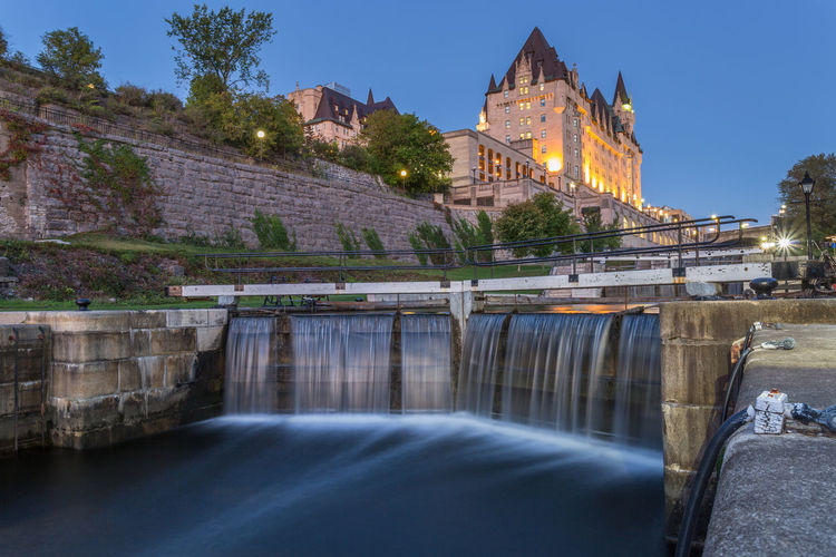 Blurred motion of rideau canal against chateau laurier hotel at dusk