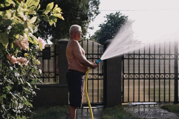 Shirtless man holding hose while standing in garden