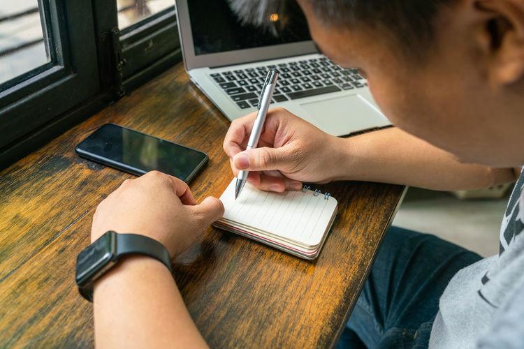 Man writing in notepad at table