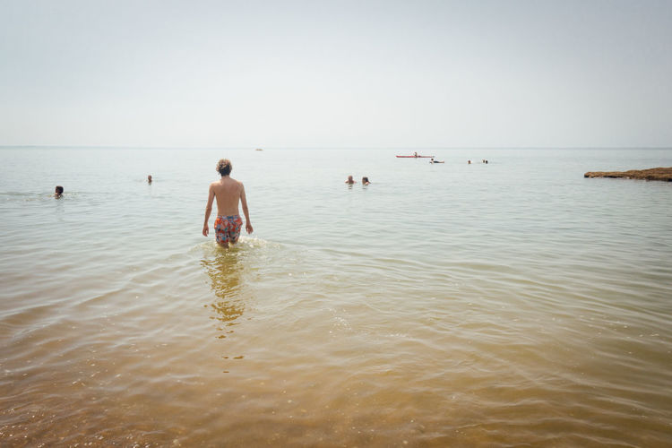Rear view of man standing in sea against clear sky
