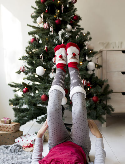 Low section of girl with feet on christmas tree