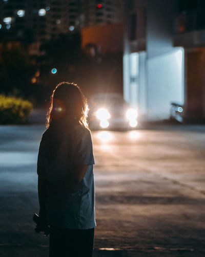 Girl standing on street at night