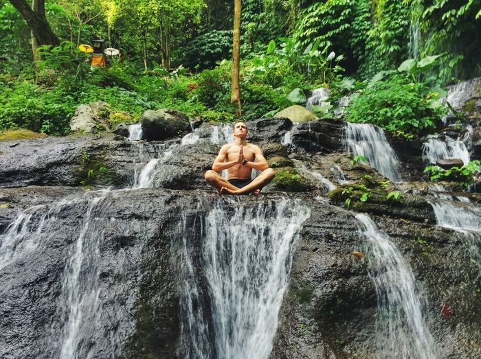 Bali Flowing Flowing Water Forest Garden Jungle Leisure Activity Lifestyles Hidden Gems  Meditation Motion Nature Nature Person Quiet Moments Real People Relaxing Rock - Object Splashing Tree Vacations Water Waterfall Yoga Young Adult