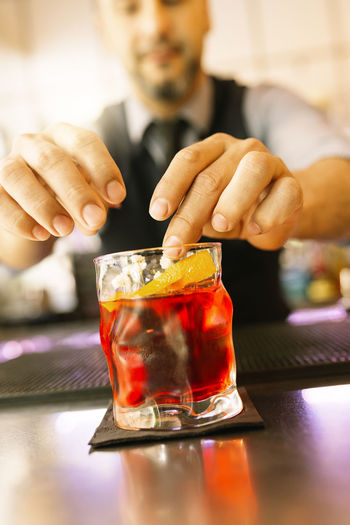 Bartender Serving Red Drink In Glass At Counter