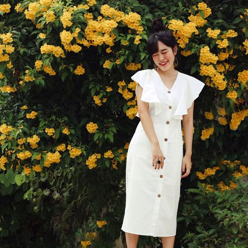 Full length of woman standing on yellow flowering plants