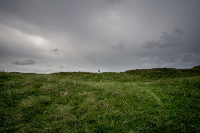Man in dunes of denmark Denmark Dunes Adult Animal Themes Cloud - Sky Day Field Grass Landscape Mammal Nature One Person Outdoors People Sky Storm Cloud The Week On EyeEm Lost In The Landscape Perspectives On Nature