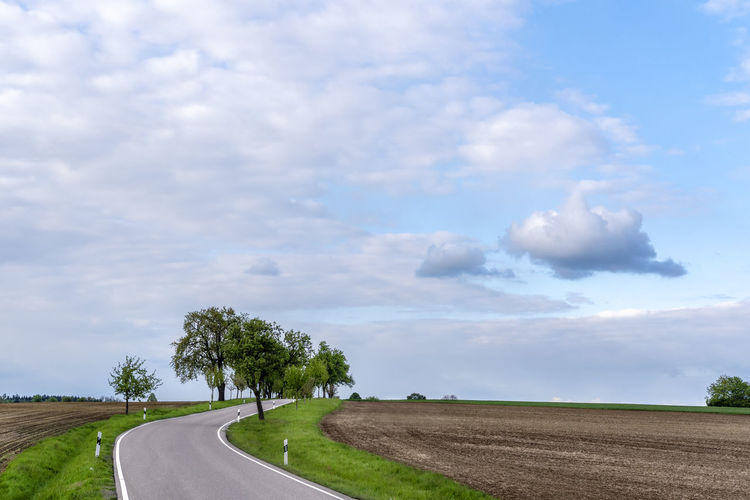 Empty road passing through agricultural fields under the blue sky with white clouds Cloud - Sky Sky Road Transportation Tree Direction The Way Forward Nature Environment Landscape Scenics - Nature No People Tranquil Scene Tranquility Land Empty Road Non-urban Scene Outdoors Dividing Line Long Road Blue Sky Agriculture Germany Green Grass Street Way