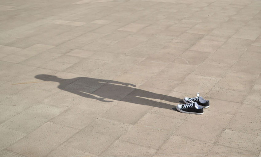 Shoes with human shadow on ground