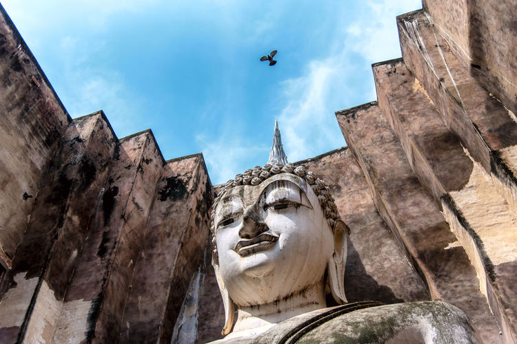 Low angle view of statue by historical building against sky
