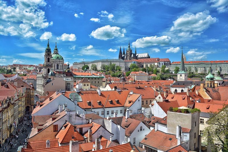 High Angle View Of Buildings And Prague Castle Against Blue Sky