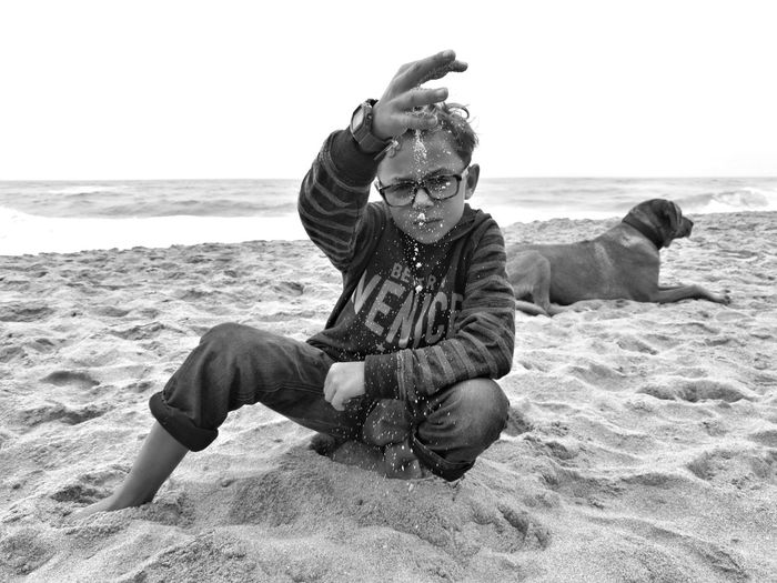 Boy Playing With Sand By Dog At Beach