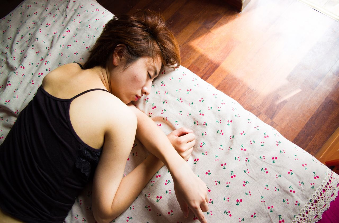 HIGH ANGLE VIEW OF BEAUTIFUL YOUNG WOMAN LYING ON FLOOR