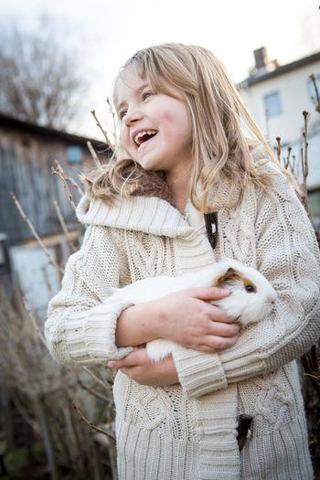 Smiling girl carrying rabbit in yard