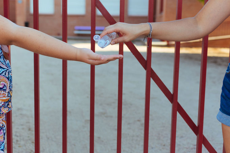Cropped image of mother pouring hand sanitizer on daughters hand