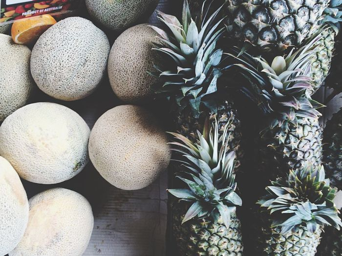 High angle view of cantaloupe and pineapple for sale in market