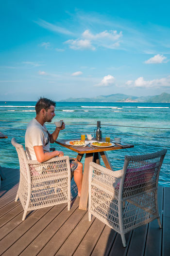 Man having drink while sitting at beach