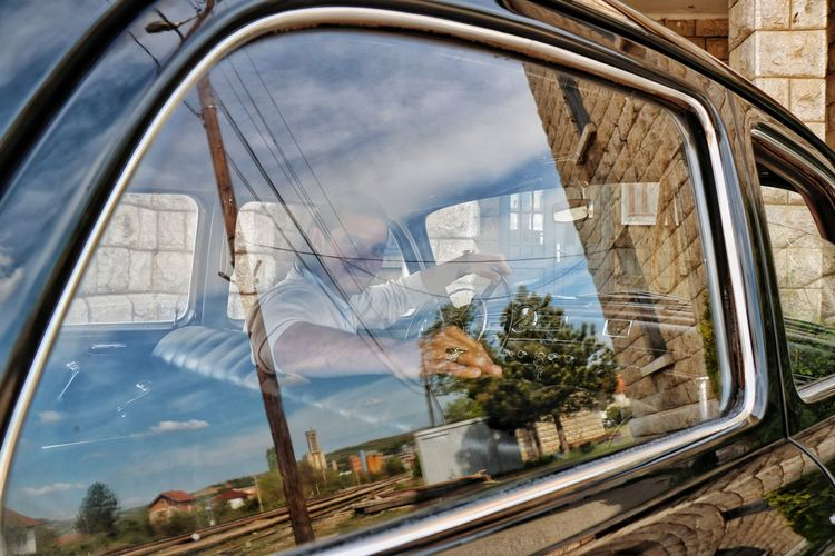 Portrait of man sitting in vintage car seen through window