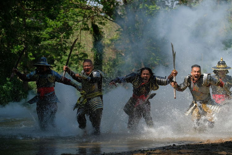 Male warriors with weapons running in lake at forest