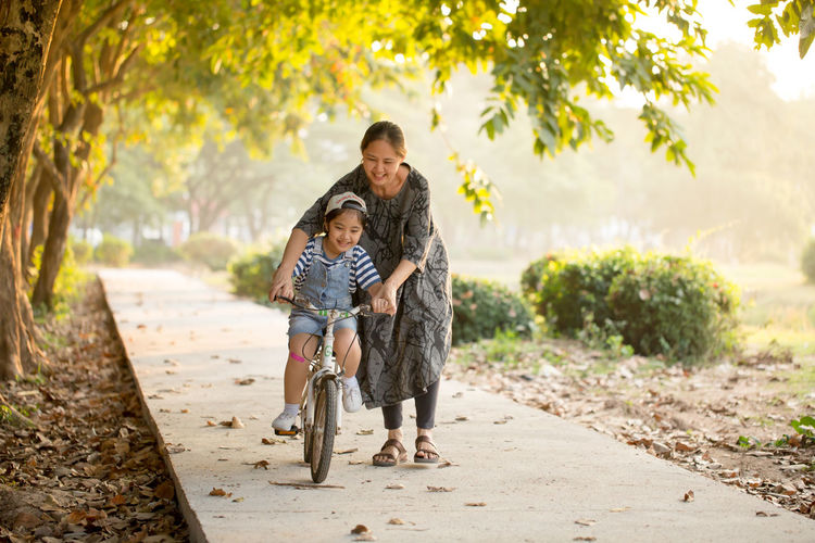Smiling Mother Teaching Daughter To Ride Bicycle On Footpath At Park